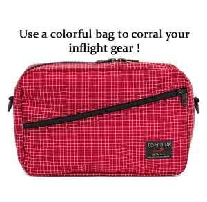 Keep your long flight travel essentials at hand by preparing a flight bag. Choose a colorful one to ensure you don't leave it behind. Packing cube shoulder bag by Tom Bihn.