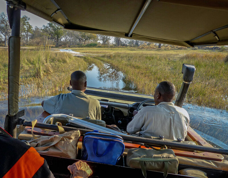safari trucks drive through the high water of the Okavango Delta