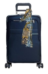 Pack light with a capsule wardrobe. Travel with carry-on only, using scarves and jewelry to add color. Image of luggage with scarf