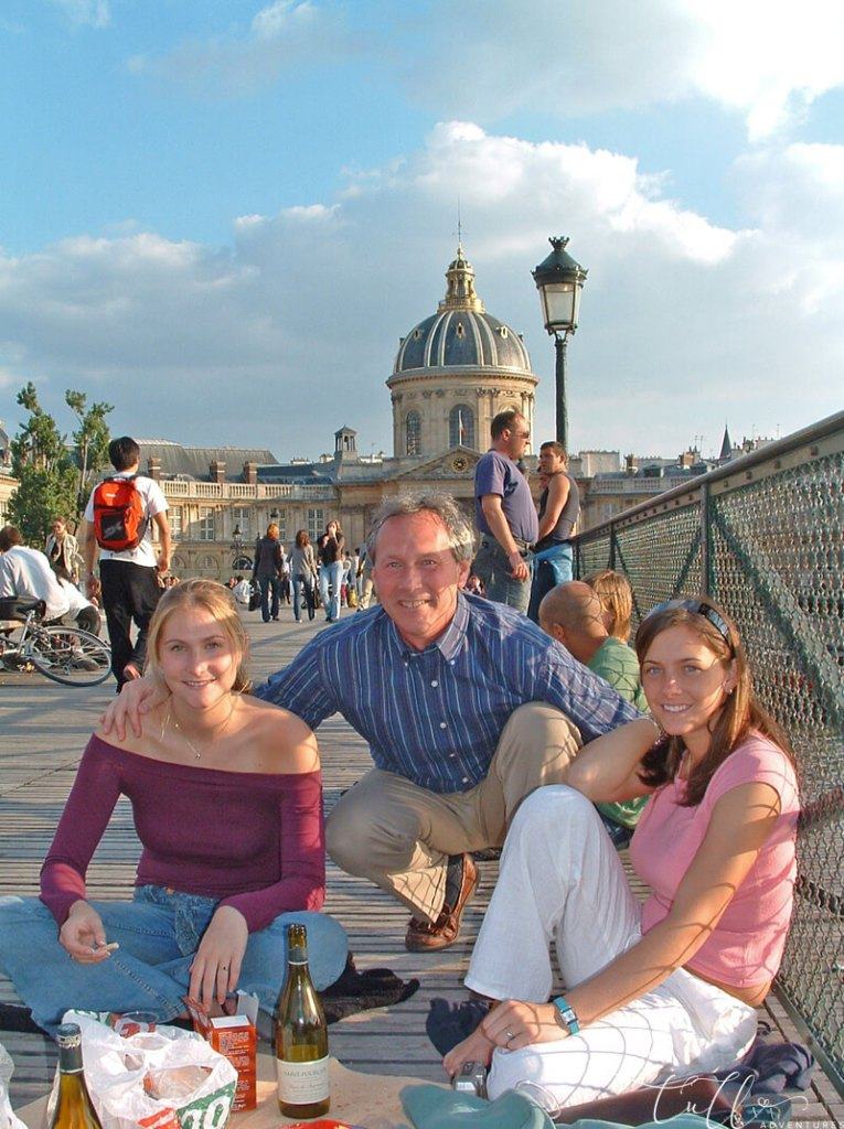 Tips for traveling with family - Buy food for a picnic along the way. Image of a family on a Parisian bridge.