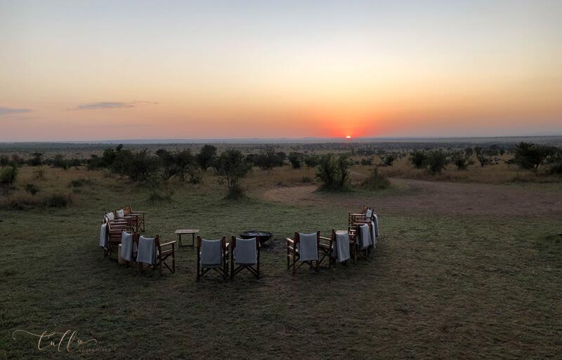 Sunrise over the Serengeti with semi-circle of chairs around firepit, Tanzania